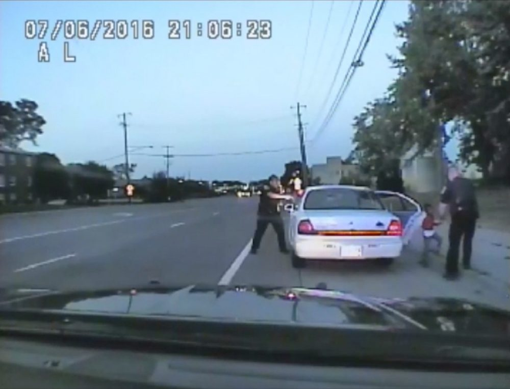 In this image made from July 6, 2016, video captured by a camera in the squad car of St. Anthony Police officer Jeronimo Yanez, the Minnesota police officer is shown after shooting into the vehicle at Philando Castile during a traffic stop in Falcon Heights, Minn., as the 4-year-old daughter of Castile's girlfriend, Diamond Reynolds, starts to get out of the car and is grabbed by an officer. (St. Anthony Police Department via AP)