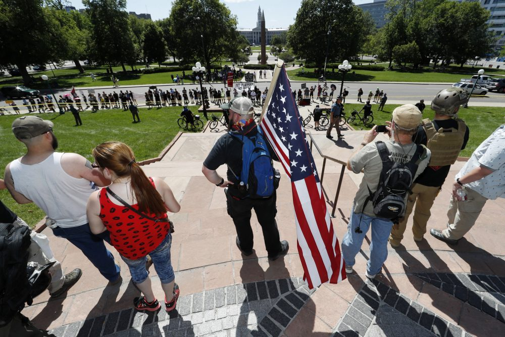 "Protesters against Muslims wave American Flags during a ""March Against Sharia"" promoted by ACT for America! Saturday, June 10, 2017, on the grounds of the State Capitol in Denver. (David Zalubowski/AP)"
