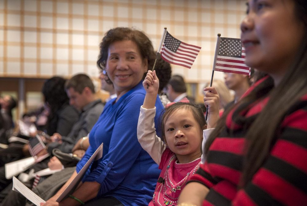 Annie Lau, 4, waves flags at her grandmother's naturalization ceremony at the JFK Library in Boston in March 2017. (Robin Lubbock/WBUR)