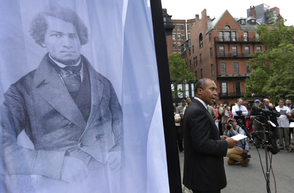Former Massachusetts Gov. Deval Patrick stands next to a likeness of abolitionist leader Frederick Douglass while participating in a community reading of Douglass' speech on the Boston Common, July 2, 2013. (Steven Senne/AP)