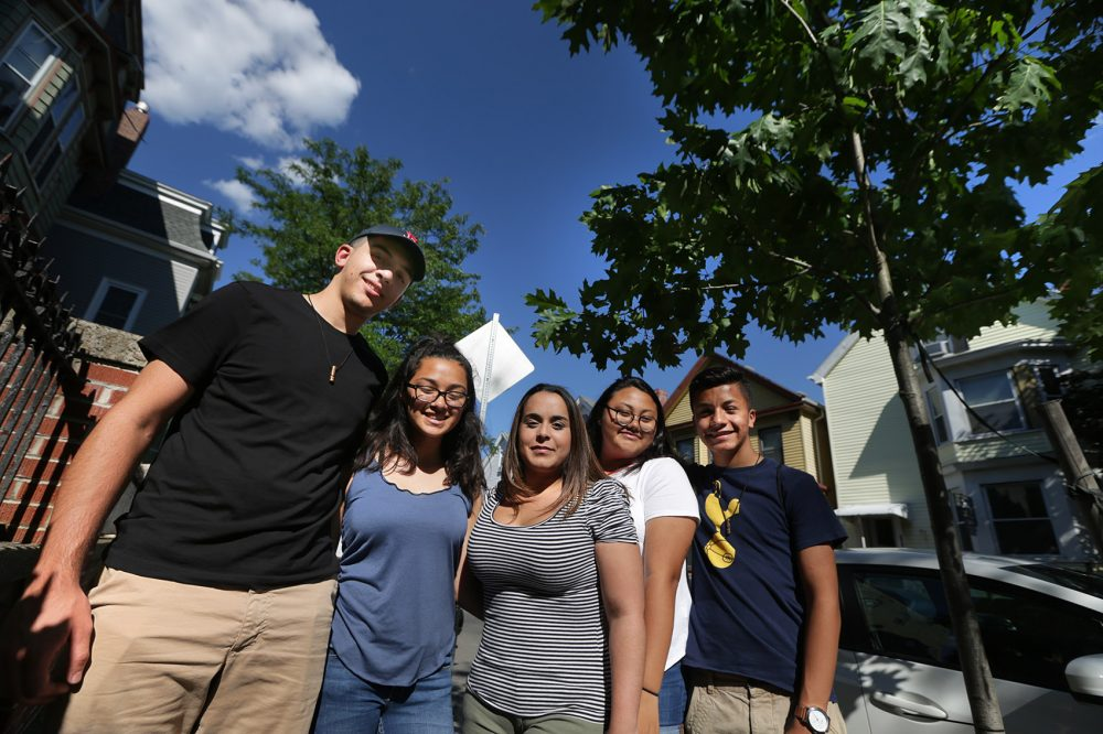 Members of NOAH's Climate CARE Tree Program team stand by an oak tree on Lexington Street, the first tree planted during the project. From left: Michael Passariello, Jenn Pineda, NOAH Community Engagement Coordinator Melinda Vega, Gabriela Ramirez and Stephan Marin. (Jesse Costa/WBUR)