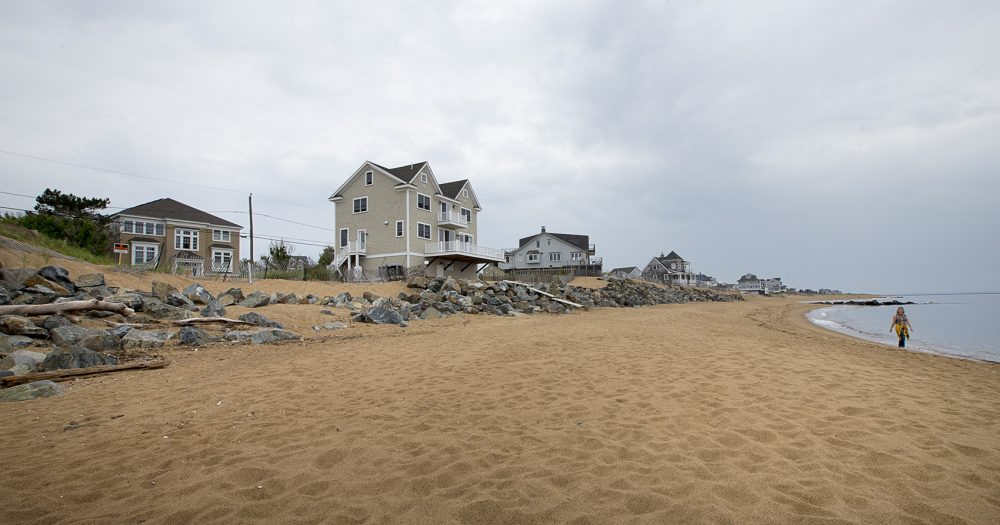 On the left is an empty lot where a beach house once stood. Successive storms during 2013 took it down. The owner has not rebuilt the house. (Jesse Costa/WBUR)