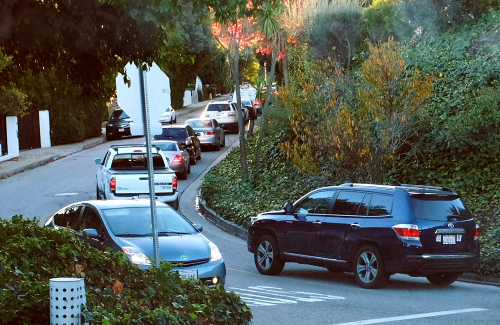 Early morning rush-hour traffic winds its way along a narrow street in the Sherman Oaks section of Los Angeles in 2014. When the people whose houses hug the narrow warren of streets paralleling the busiest urban freeway in America began to see bumper-to-bumper traffic rushing by their homes, they were baffled. When word spread that the explosively popular smartphone app Waze was sending many of those cars through their neighborhood in a quest to shave five minutes off a daily rush-hour commute, they were angry and ready to fight back. (Richard Vogel/AP)