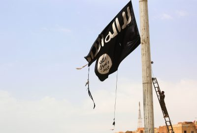 A member of the U.S.-backed Syrian Democratic Forces removes an Islamic State group flag in the town of Tabqa, about 55 kilometres (35 miles) west of Raqqa, on April 30, 2017. (Delil Souleiman/AFP/Getty Images)