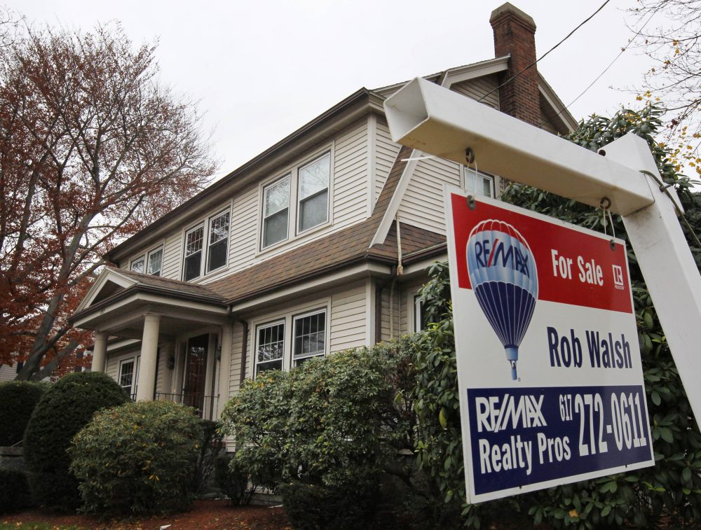 A rare sight these days: In this 2011 file photo, a for sale sign hangs in front of a home in Milton. (Steven Senne/AP)