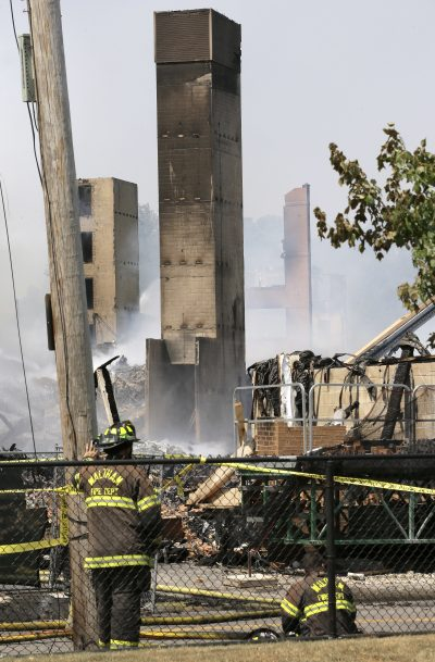 Firefighters pause near the destroyed remains of an under-construction apartment complex Sunday in Waltham. (Steven Senne/AP)