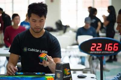 In addition to engineering speedcubes, Chris Tran has competed in many a speedcubing event. Here, he solves the cube one-handed. (Courtesy Chris Tran)