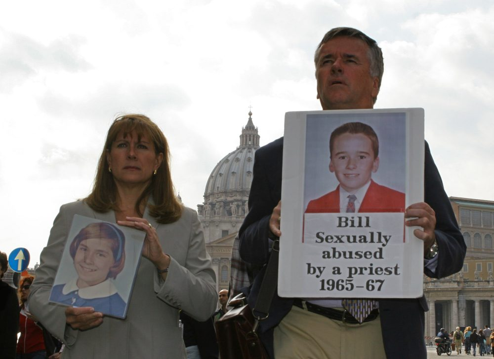 Advocates for victims of clergy sex abuse, Barbara Blaine from Chicago, Ill., and Bill Gately, from Boston, Mass., hold pictures of themselves at the age of 12 and 14 respectively when they were allegedly sexually abused by clergymen, at a protest near St. Peter's Square in Rome in 2005. (Alessandra Tarantino/AP)