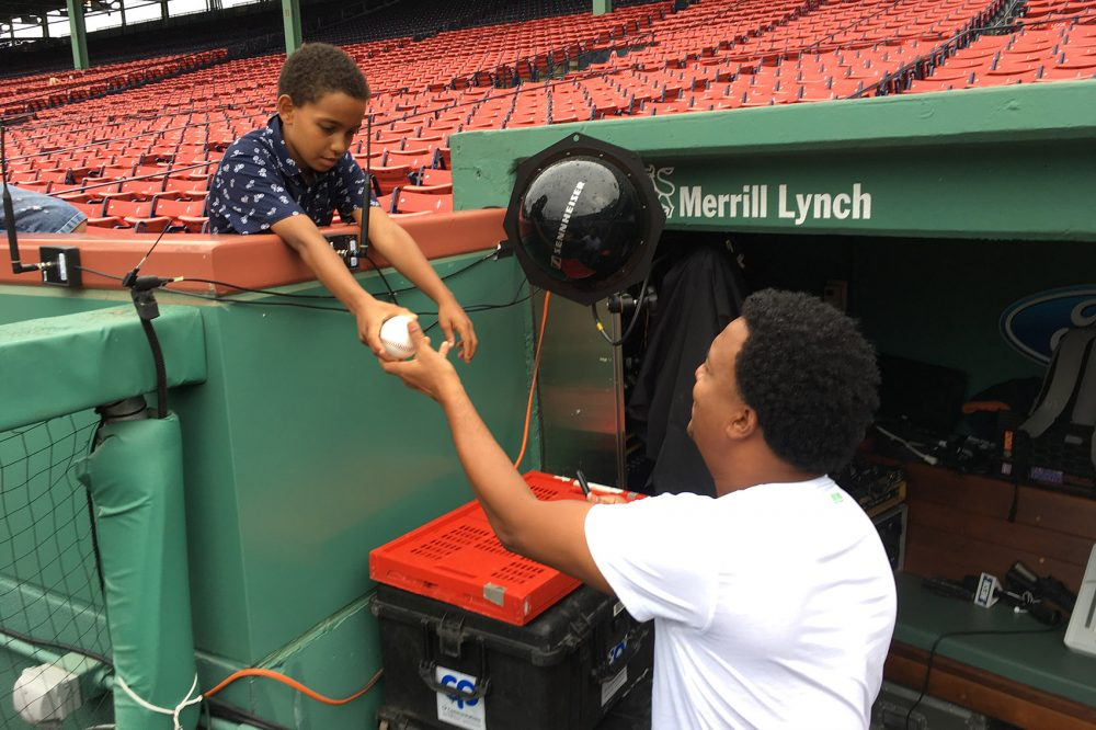 Former Boston Red Sox pitcher Pedro Martinez autographs a ball for a young fan at Fenway Park. (Lynn Jolicoeur/WBUR)