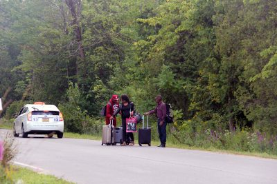 Three people from Haiti make their way to the Roxham Road crossing in a taxi. One of the young men had been living in San Diego for over a year, but is looking for asylum in Canada. (Kathleen Masterson/VPR)