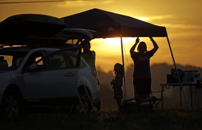 A family sets up a tent at their campsite at sunrise for the solar eclipse Monday, Aug. 21, 2017, on the Orchard Dale historical farm near Hopkinsville, Ky. The location, which is in the path of totality, is also at the point of greatest intensity. (Mark Humphrey/AP)