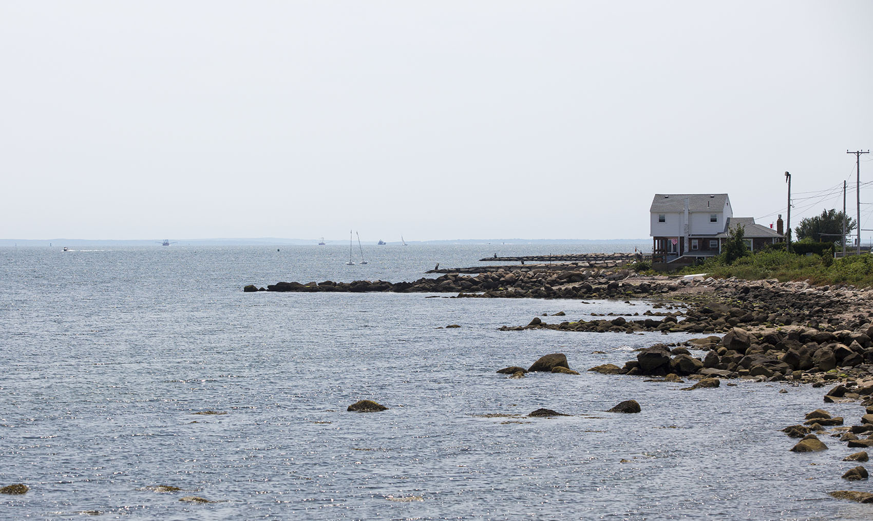 Volunteers and staffers with the Buzzards Bay Coalition have been collecting water quality data for decades in an effort to help the struggling bay. Now they're teaming up with with the Woods Hole Oceanographic Institution to use the data to help fight climate change. Here, a house sits on the rocky north end of East Beach in New Bedford overlooking Buzzards Bay. (Jesse Costa/WBUR)