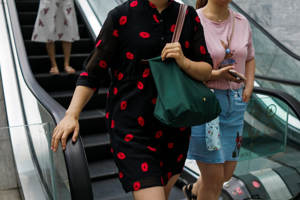Chinese women descend from an escalator in the Lujiazui Financial District in Pudong in Shanghai, on Aug. 1, 2017. (Chandan Khanna/AFP/Getty Images)