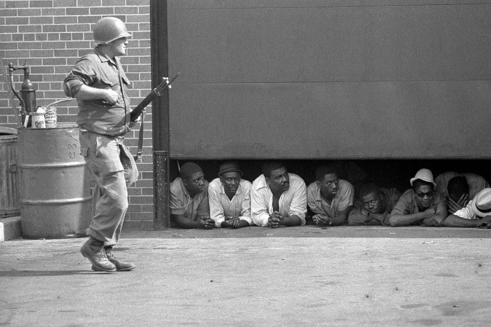 In this July 26, 1967 file photo, an Army soldier stands guard as men captured in the vicinity of the 10th Police Precinct in Detroit peer from under a garage door awaiting transfer. Five days of violence would leave 33 blacks and 10 whites dead, and more than 1,400 buildings burned. More than 7,000 people were arrested. (AP)