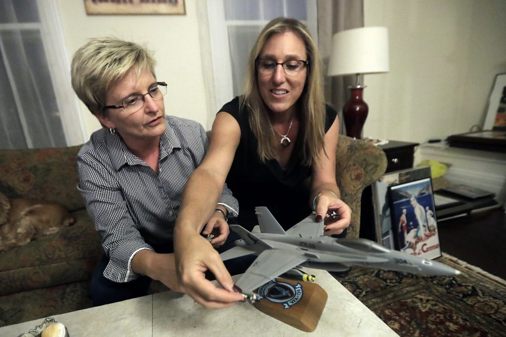 "Alaina Kupec, right, and her wife Kathy Brennan work a model F18 jet in the home they just moved in to, on July 26 in Orange, N.J. Kupec, a transgender woman who worked with pilots who flew F18 jets while serving as a Navy intelligence officer from 1992 until 1995, said she felt ""heartbreak"" after she heard about Trump's pronouncement banning transgender people from military service. The 48-year-old publicly transitioned to life as a woman in 2013. (Julio Cortez/AP)"