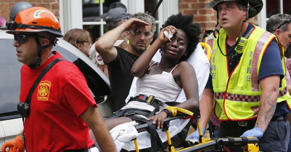 Rescue personnel help an injured woman after a car ran into a large group of protesters after an white nationalist rally in Charlottesville, Va., Saturday, Aug. 12, 2017. (Steve Helber/AP)