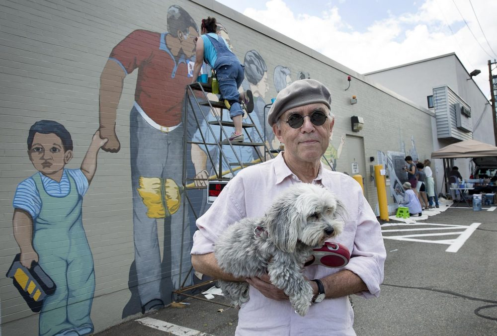 "Artist Bernie LaCasse, 74, with his dog Misty Moonlight in front of his ""Beat the Belt"" mural in Cambridgeport. (Robin Lubbock/WBUR)"