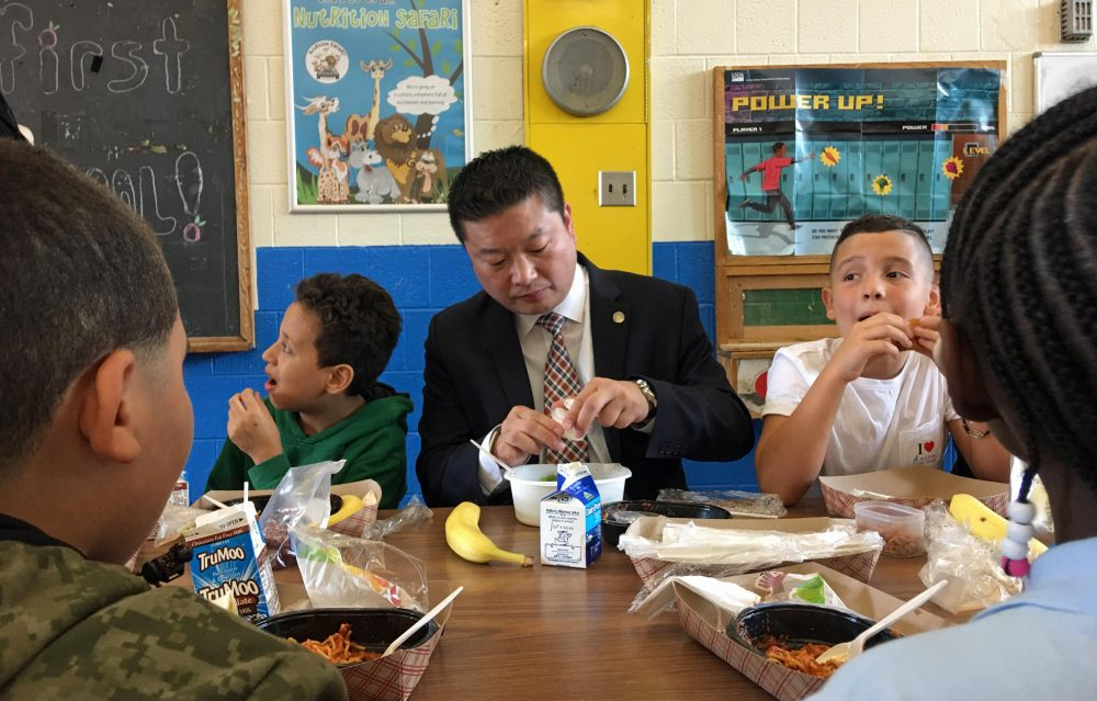 Boston Public Schools Superintendent Tommy Chang tries the new lunches at the Blackstone School in the South End on the first day of school Thursday. (Max Larkin/WBUR)