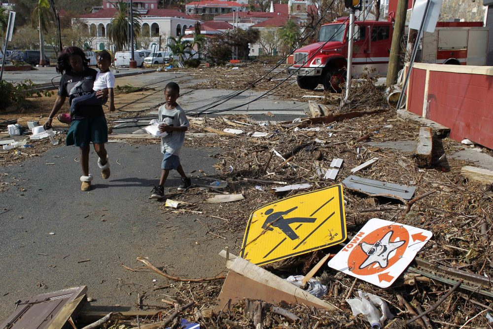 A woman with her two children walk past debris left by Hurricane Irma in Charlotte Amalie, St. Thomas, U.S. Virgin Islands, Sunday, Sept. 10, 2017. (Ricardo Arduengo/AP)