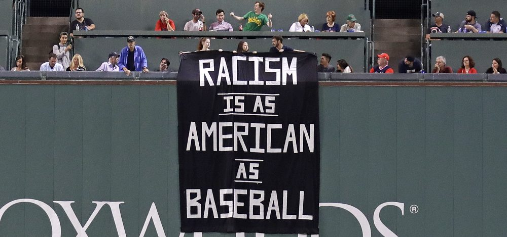 A banner is unfurled over the left field wall during the fourth inning of a baseball game between the Boston Red Sox and Oakland Athletics at Fenway Park in Boston on Wednesday. (Charles Krupa/AP)