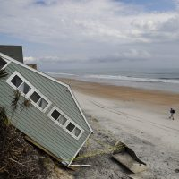 A house rests on the beach after collapsing off a cliff from Hurricane Irma in Vilano Beach, Fla. on Sept. 15. Florida's economy has long thrived on one major import: people. Irma raised concerns about just how sustainable the allure of Florida's year-round warmth and lifestyle are. (David Goldman/AP)