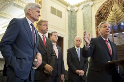 Sen. Lindsey Graham (right), R-S.C., stands with Sen. Bill Cassidy (left), R-La., Sen. Dean Heller (second from left), R-Nev., and Sen. Ron Johnson (second from right), R-Wisc., as well as former Sen. Rick Santorum (center) to announce their legislation to repeal and replace the Affordable Care Act through block grants on Capitol Hill in Washington, D.C., on Sept. 13, 2017. (Jim Watson/AFP/Getty Images)