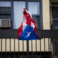 A Puerto Rican flag hung from the balcony of a West Dedham Street apartment building. (Jesse Costa/WBUR)