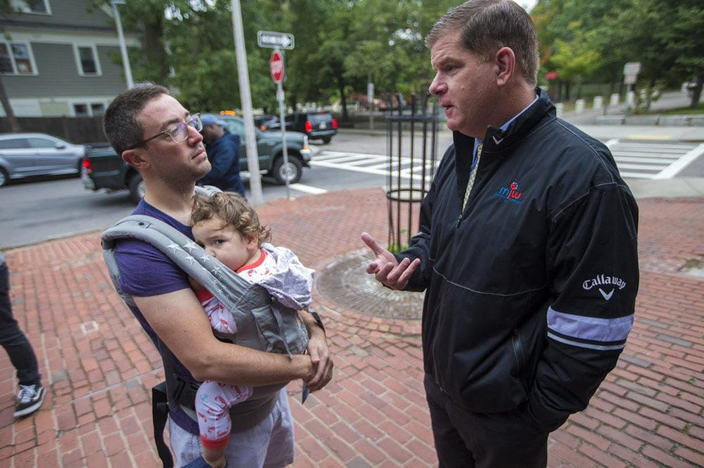 Boston Mayor Marty Walsh speaks with Jamaica Plain resident Eliav Kahan outside Green Street Station ahead of the upcoming preliminary election. (Jesse Costa/WBUR)