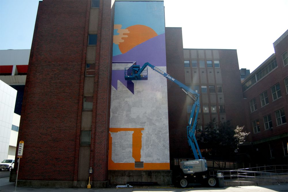 Tim McCool works on his sunrise mural during the last week of September at 774 Albany St., Boston. (Greg Cook/WBUR)