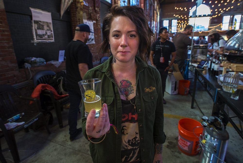 Sara Maya, of Fonta Flora Brewery, holds a glass of Brutus Farmhouse Ale. (Jesse Costa/WBUR)