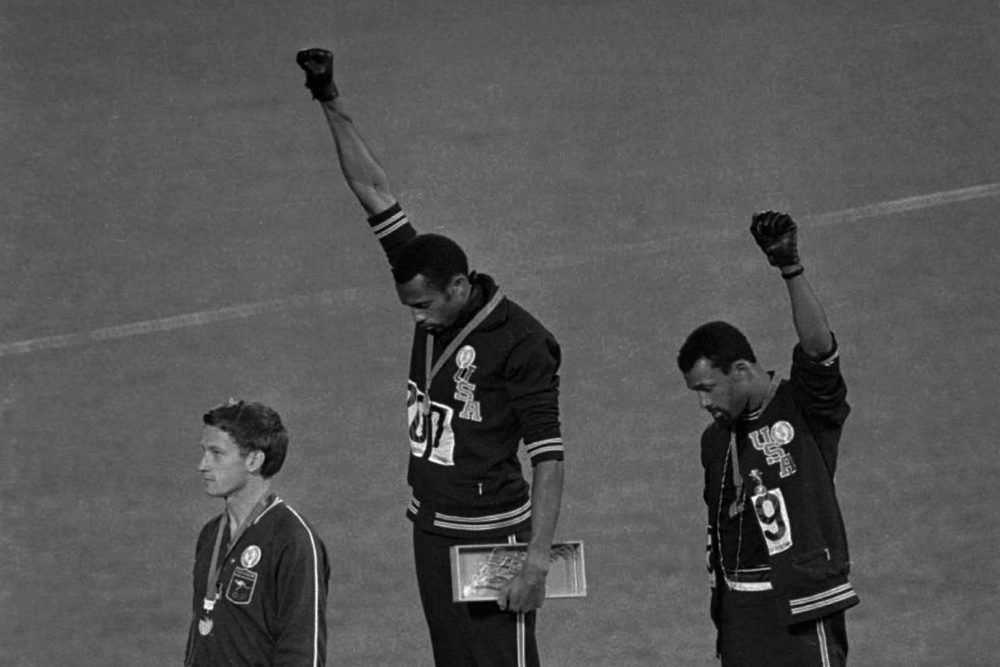 "Extending gloved hands skyward in racial protest, U.S. athletes Tommie Smith, center, and John Carlos stare downward during the playing of ""The Star-Spangled Banner"" after Smith received the gold and Carlos the bronze for the 200-meter run at the Summer Olympic Games in Mexico City on Oct. 16, 1968. (AP)"