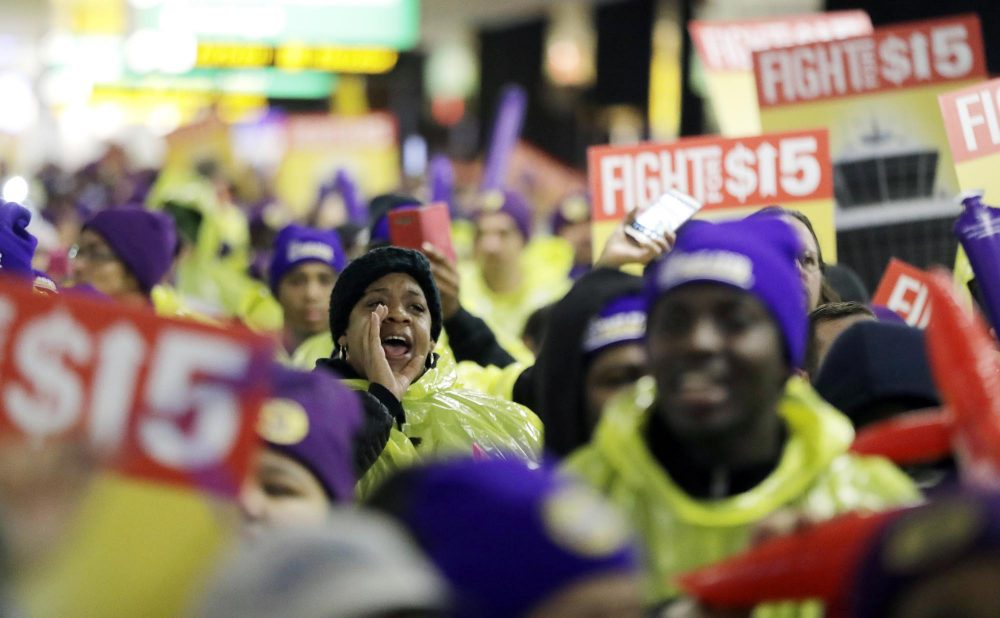 A woman shouts while marching with service workers asking for $15 minimum wage pay during a rally at Newark Liberty International Airport in New Jersey in 2016. (Julio Cortez/AP)