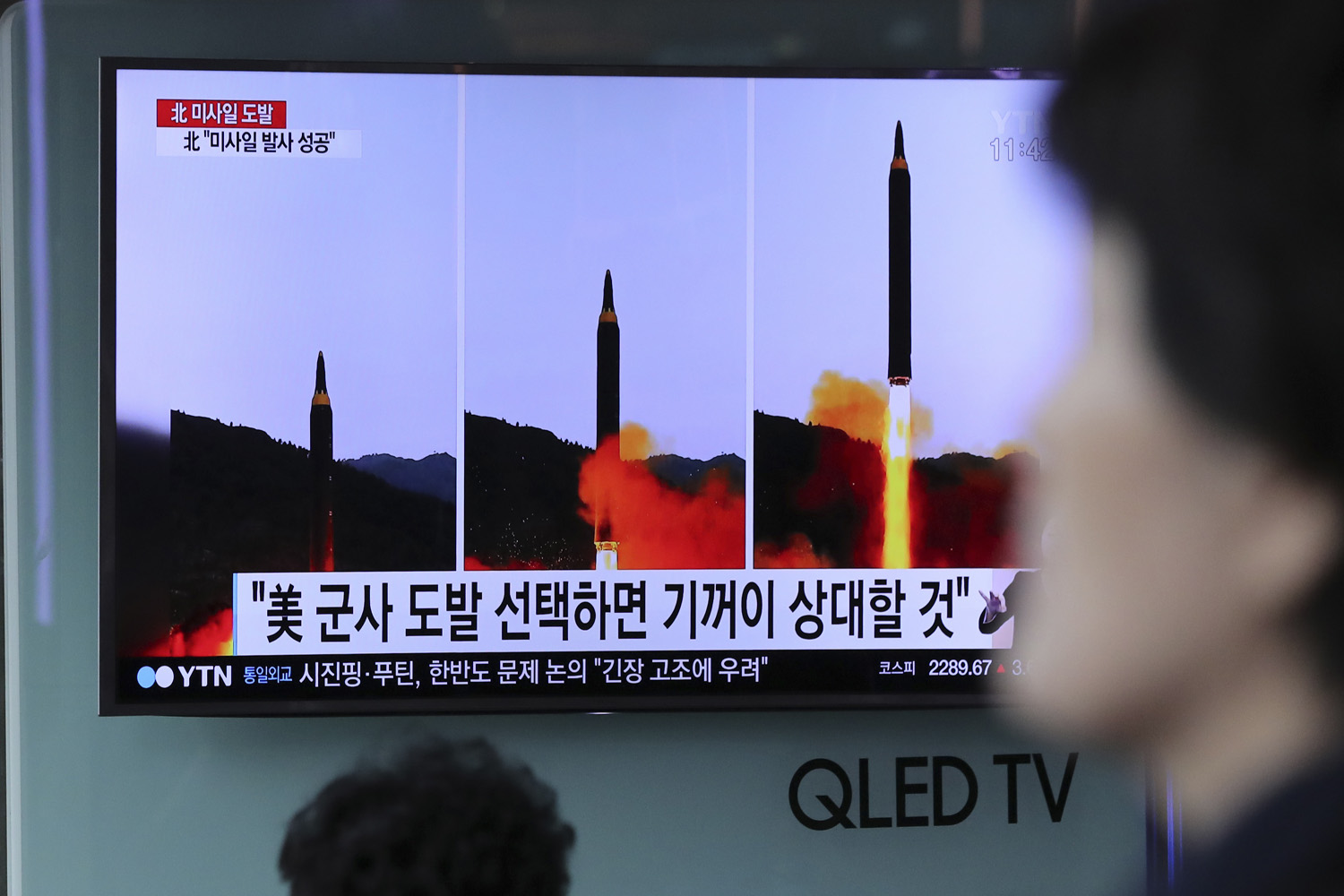 A woman walks by a TV news program showing images of North Korean missile launch, published in the country's Rodong Sinmun newspaper, at Seoul Railway station in Seoul, South Korea, Monday, May 15, 2017. (Lee Jin-man/AP)