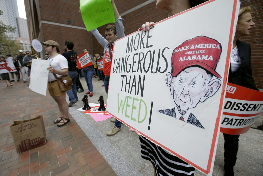 Jean Inglis, of Nahant, Mass., holds a sign depicting Attorney General Jeff Sessions as she protests Thursday with others outside the federal courthouse in Boston where Sessions was speaking to law enforcement officials about international organized crime. (Steven Senne/AP)