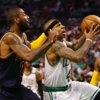 Isaiah Thomas, formerly of the Boston Celtics, drives to the basket against Kyrie Irving, formerly of the Cleveland Cavaliers, in the 2017 NBA playoffs. The players have swapped jerseys after a recent blockbuster trade.  (Elsa/Getty Images)