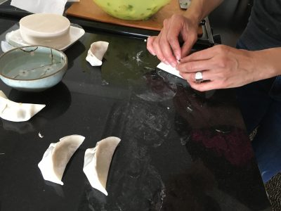 Joanne Chang demonstrates how her mother pleats dumplings. (Meghna Chakrabarti/WBUR)