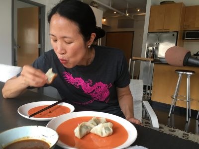 Joanne Chang enjoys the pork and chive dumplings (Meghna Chakrabarti/WBUR)