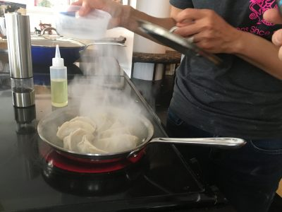 Adding water to the skillet in order to steam the dumplings. (Meghna Chakrabarti/WBUR)