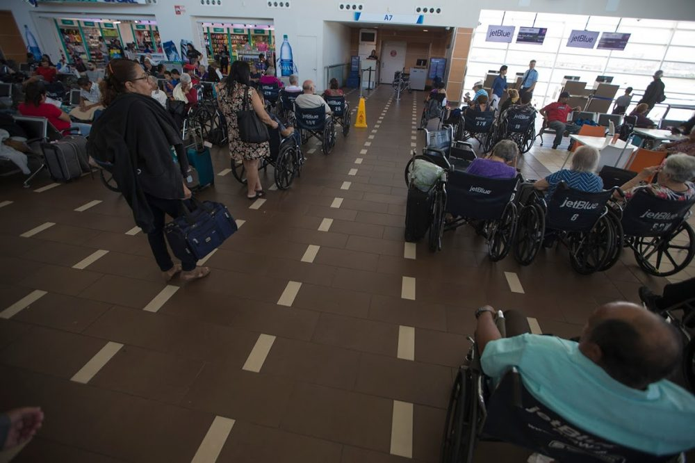 Airline travelers in wheelchairs wait to board the next flight out of Luis Muñoz Marin Airport in San Juan. (Jesse Costa/WBUR)