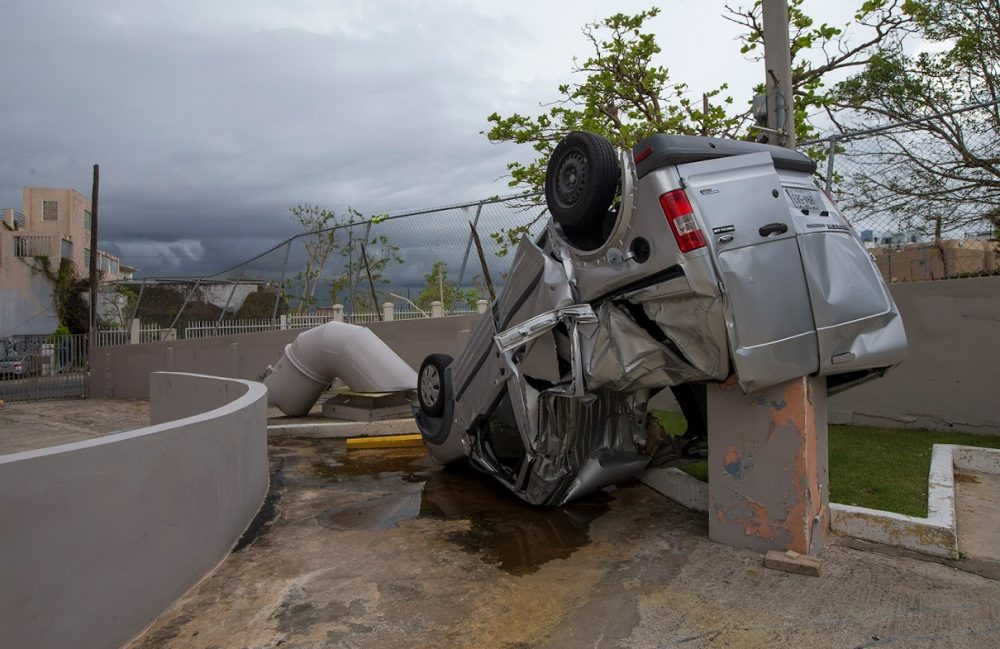 A van was thrown and overturned during Hurricane Maria in a parking lot behind La Inmaculada Elderly Center in San Juan. (Jesse Costa/WBUR)