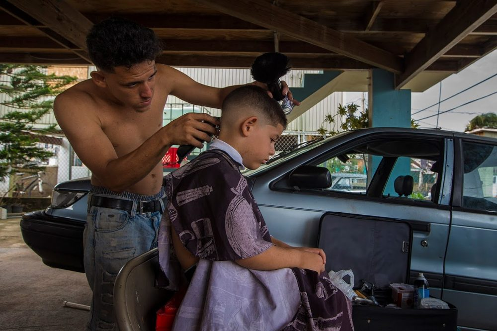 In the Juana Matos community in Cataño, Cristhian Llopiz gives haircuts to his neighbors in the area. (Jesse Costa/WBUR)