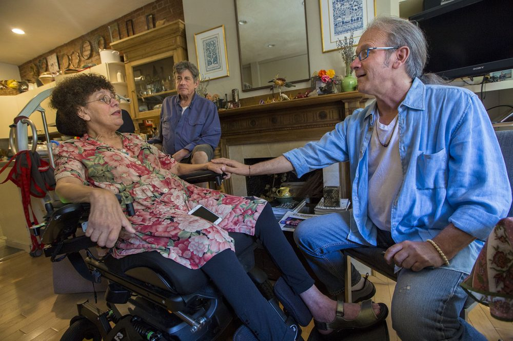 Ron Hoffman, right, visits the Boston home of Susan Kron, who has ALS, and her husband Paul Schaffrath. (Jesse Costa/WBUR)