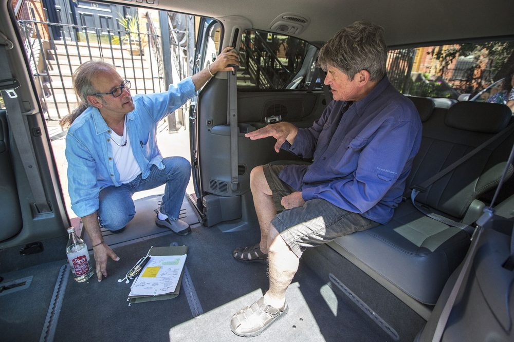 Hoffman and Schaffrath discuss additional alterations to the van that can be made to better serve Kron traveling in her wheelchair. (Jesse Costa/WBUR)