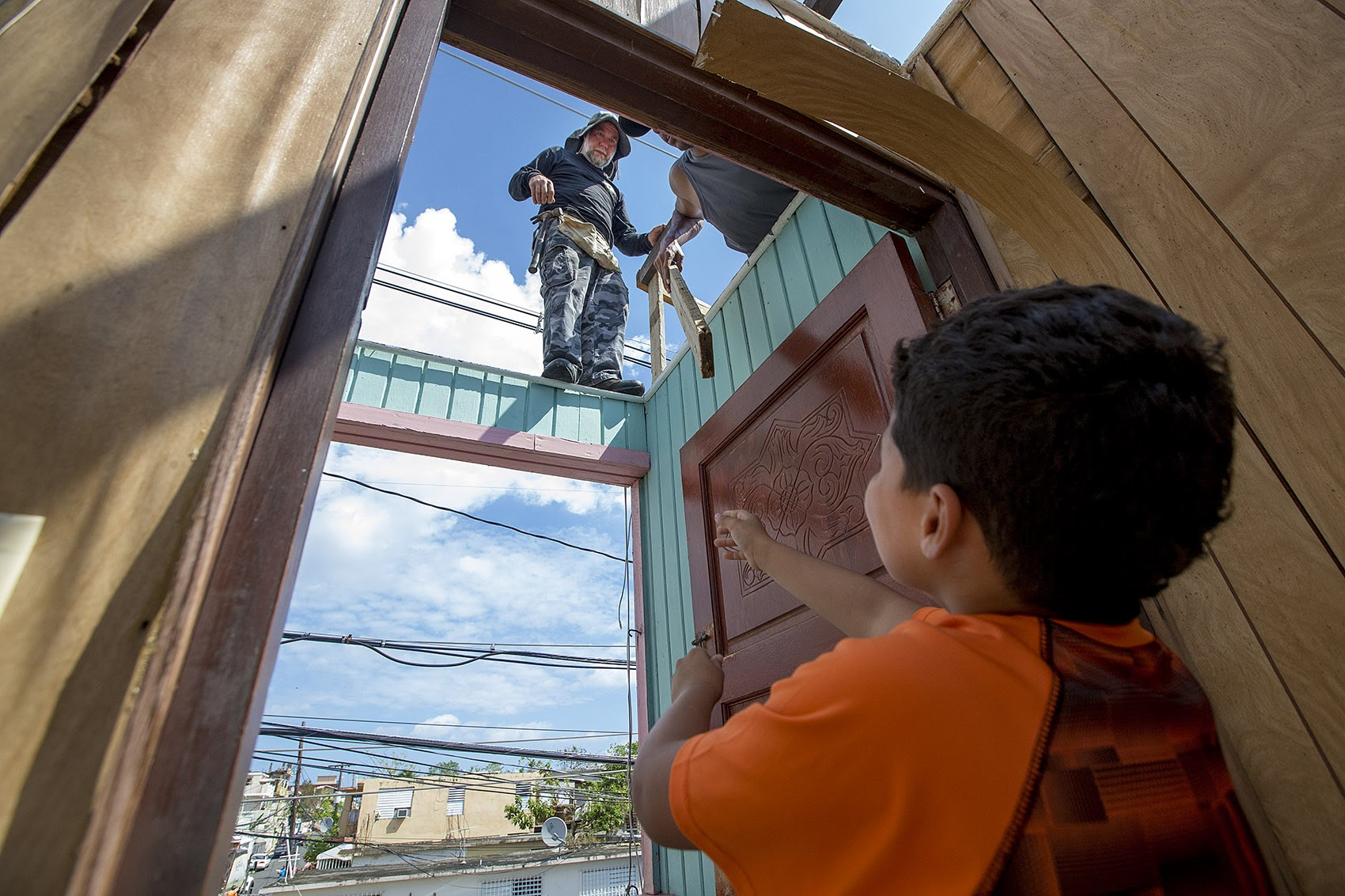 Jose Lopez hands a small board to Anthony Geigel and Israel Garcia to repair their roof in Barrio Obrero Santurce. (Jesse Costa/WBUR)