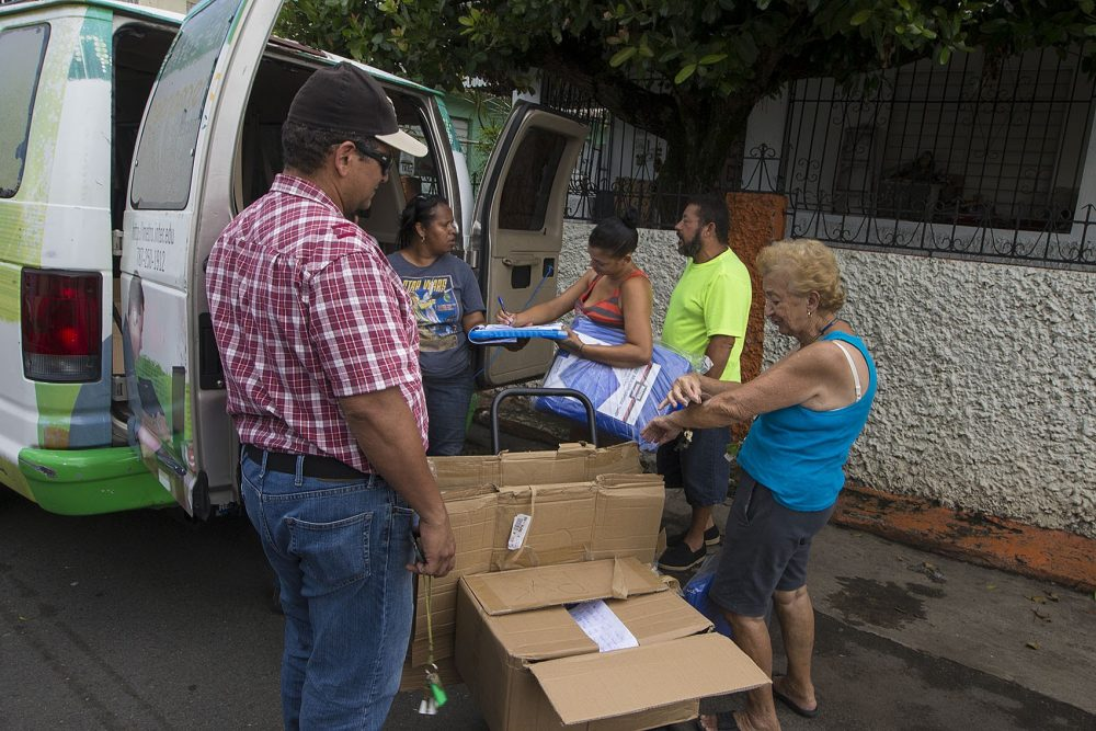 On the streets of Barrio Obrero Santurce, workers from Proyecto Enlace distribute tarps for residents who have roof damage caused by Hurricane Maria. (Jesse Costa/WBUR)