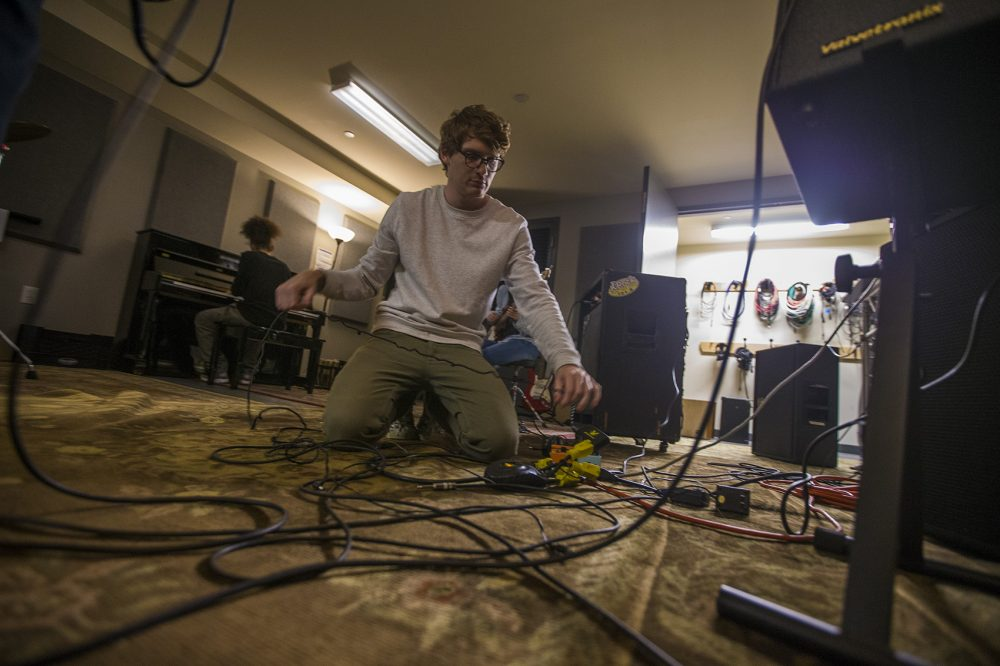 Wes Kaplan works on guitar pedals at the Brookline Teen Center so the band Detour can rehearse ahead of Yes Fest. (Jesse Costa/WBUR)