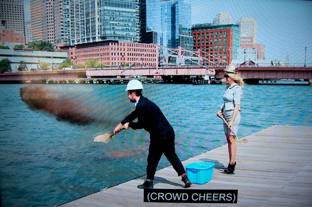 "Pat Falco shovels dirt into Boston's Fort Point Channel in a video purporting to show the groundbreaking of the ""Luxury Waters"" condo tower. (Greg Cook/WBUR)"
