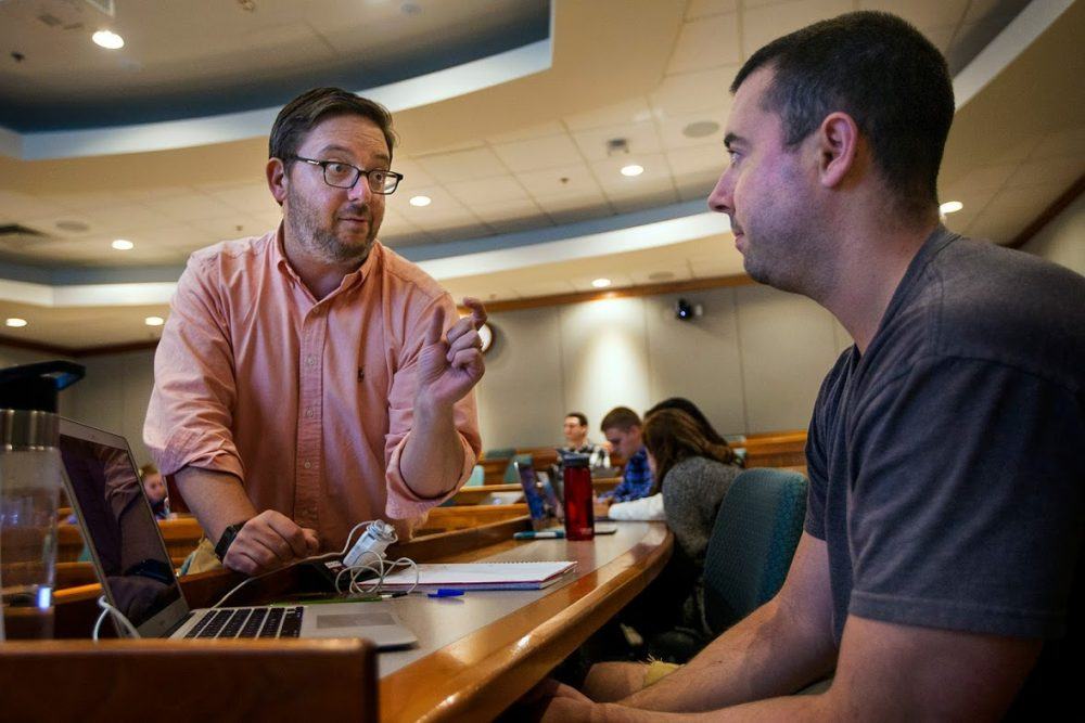 "Suffolk Law School professor Gabe Teninbaum, left, talks with a student during class. Teninbaum teaches a course called ""Lawyering in the Age of Smart Machines."" (Jesse Costa/WBUR)"