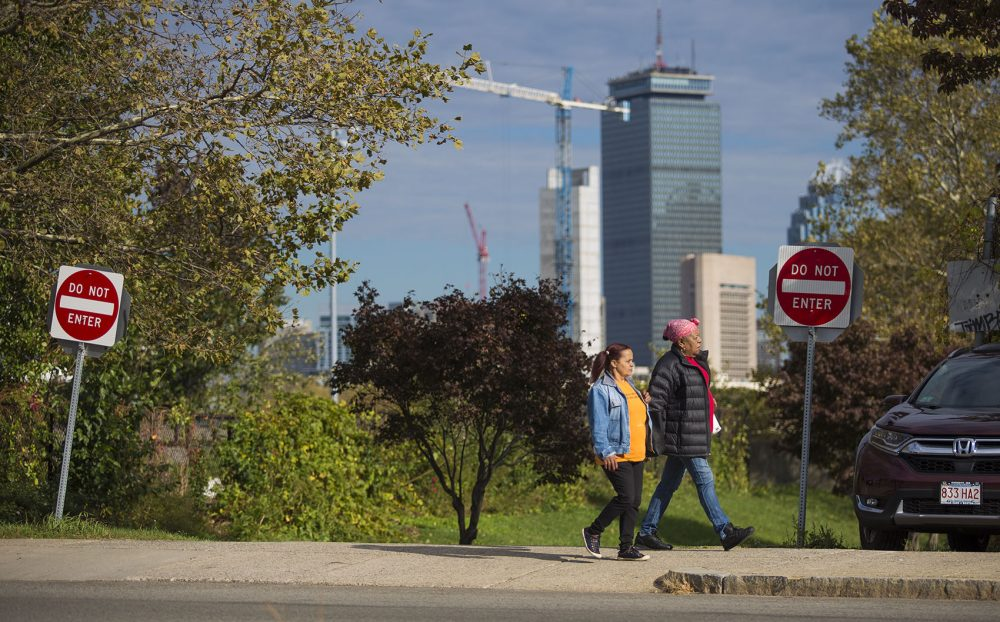 Two women walk down the street along Malcolm X Boulevard in Roxbury, with downtown Boston in the background. (Jesse Costa/WBUR)