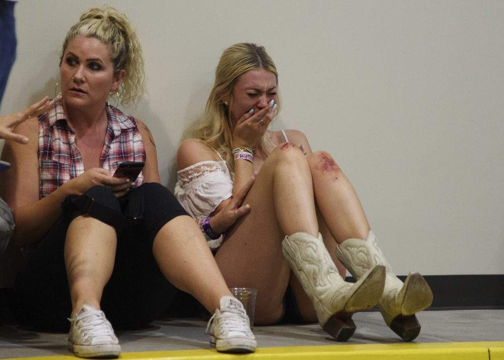 A woman cries while hiding inside the Sands Corporation plane hangar after a mass shooting in which dozens were killed at the Route 91 Harvest Festival on Sunday, Oct. 1, 2017, in Las Vegas. (Al Powers/Invision/AP)